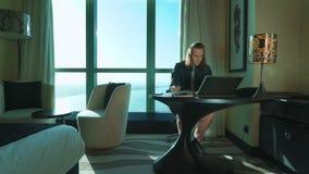 Den unga affärsmannen med långt hår arbetar på bärbara datorn, skriver texten, tänker i regeringsställning eller hotellrum Chef f stock video