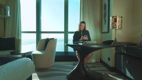 Den unga affärsmannen med långt hår arbetar på minnestavlan, skriver texten, tänker, stannar till mobiltelefonen hemmastatt, kont stock video