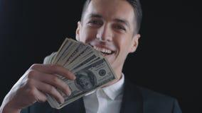 Den unga affärsmannen med mycket dollarräkningar är lycklig om vinst eller lön lager videofilmer