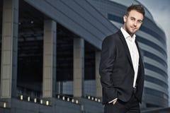 Den unga affärsmannen poserar utomhus-. royaltyfri fotografi