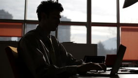 Den unga affärsmannen räcker maskinskrivning på bärbara datorn