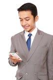 Den unga affärsmannen skrev ett meddelande med en telefon Royaltyfri Bild