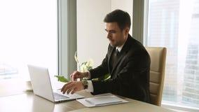 Den unga affärsmannen som avslutar arbetsdagspå allt kontoret, arbetar gjort stock video