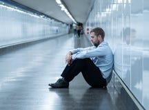Den unga affärsmannen som gråt övergav, förlorade i fördjupningen som sitter på jordgångtunnelen royaltyfria foton