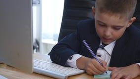 Den unga affärsmannen som i regeringsställning använder en dator och, gör anmärkningar stock video