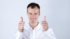 den unga affärsmannen visar upp tummar med båda händer, medan le Arkivbild