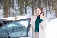 Den unga aff?rskvinnan talar p? en telefon f?rutom hennes bil arkivfoton