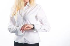 Den unga affärskvinnan kontrollerar tid på hennes armbandsur, tid, det sena begreppet, studioforsen som isoleras på vit Arkivbild