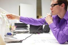 den unga affärsmanen ringer på läsning noterar i regeringsställning Arkivfoto