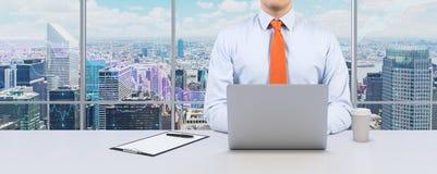 Den unga affärsmannen arbetar med bärbara datorn Modernt panorama- kontor eller arbetsställe med den New York City sikten Royaltyfria Bilder