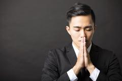 Den unga affärsmannen med ber gest Royaltyfri Fotografi