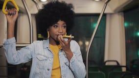Den unga afrikansk amerikankvinnan som använder smart telefonstämmaerkännande, dikterar tankar, ringande meddelanderidning för st arkivfilmer