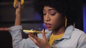Den unga afrikansk amerikankvinnan som använder smart telefonstämmaerkännande, dikterar tankar, ringande meddelanderidning för st lager videofilmer