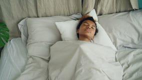 Den unga afrikansk amerikankvinnan som sover i bekväm säng under varma filten som den har, vilar på härlig linne komfort lager videofilmer