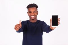 Den unga afrikansk amerikanmannen som rymmer en smartphonemaking, tummar upp arkivfoto