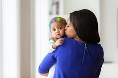 Den unga afrikansk amerikanmodern som spelar med hennes, behandla som ett barn flickan Royaltyfri Foto