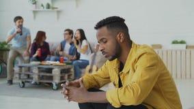 Den unga afrikanska amercan mannen känner rubbning och isolerade medan hans vänner som hemma firar partiet inomhus stock video