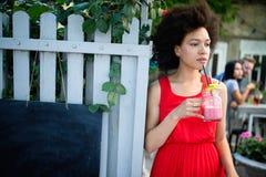 Den unga afrikanska kvinnan tycker om den sunda vegetariska smoothien för viktförlust fotografering för bildbyråer