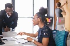 Den unga afrikanska kvinnliga ledaren är sitta och erbjuda samarbete till den afrikanska grabben Arkivfoto