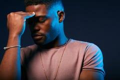 Den unga afrikanska mannen som lider från migrän, stänger hans ögon, hans lyftte till huvudet arkivbild
