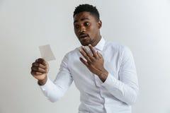 Den unga afro mannen med ett besviket olyckligt ledset uttryck förlorade en vad på grå studiobakgrund royaltyfri bild