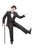 Den unga aktören i svart passar innehav en rotting och en dans Arkivbilder