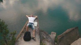 Den unga aktiva mannen kopplar av, genom att vila på, vaggar för bergsjön för lutningen near lugna yttersida med översikten som l arkivfilmer