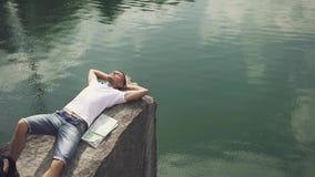 Den unga aktiva mannen kopplar av, genom att vila på, vaggar nära bergsjöyttersida med översikten som lägger bredvid honom stock video