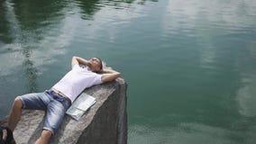 Den unga aktiva mannen kopplar av, genom att vila på, vaggar nära lugna bergsjöyttersida med översikten som lägger bredvid honom stock video
