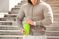 Den unga aktiva mannen ska dricka att se hans klocka, schema, utomhus Stilig muskulös manlig hållande shaker, dricksvatten Arkivfoton