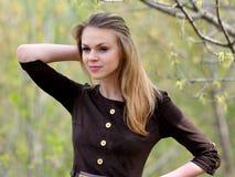 Den unga angenäma le flickan med långt hår Royaltyfria Foton
