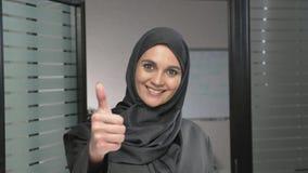 Den unga arabiska flickan i hijab visar tecknet av som, godkännande, godkännandet, oken som är trevlig 60 fps stock video