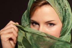 Den unga arabiska kvinnan med skyler uppvisning henne av ögondark Arkivbild