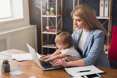 Den unga arbetande mamman som spenderar tid med, behandla som ett barn royaltyfri fotografi