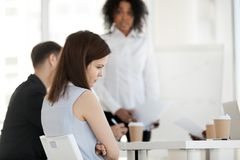 Den unga arbetaren känner kränkt frustrerat under möte på arbete royaltyfri bild