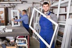 Den unga arbetaren visar PVC-tillverkningsefterbehandling Arkivbilder