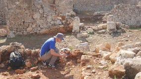 Den unga arkeologen arbetar p? en arkeologisk plats stock video