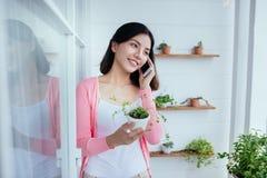 Den unga asianbeautiful flickan som talar på telefonen, stod hon förbi Royaltyfri Fotografi