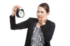 Den unga asiatiska affärskvinnan är stressad med en klocka royaltyfri foto