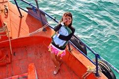 Den unga asiatiska damen ger en blinkning, som hon står på pilbågen av ett fartyg arkivfoto