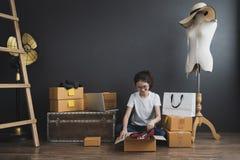 Den unga asiatiska flickan är freelanceren med hennes hemmastadda kontor för den privata affären som arbetar med bärbara datorn,  arkivbilder