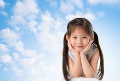 Den unga asiatiska flickan med leende på henne vänder mot Arkivfoton