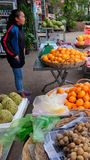Den unga asiatiska flickan säljer frukt på en stadsgata royaltyfria bilder
