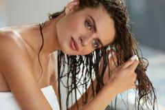 Den unga asiatiska flickan som kammar hår med, fingrar isolerat på vitbakgrund Härlig kvinna med vått hår i handduk efter bad Royaltyfria Bilder