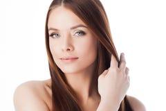 Den unga asiatiska flickan som kammar hår med, fingrar isolerat på vitbakgrund stående av en härlig flicka med långt silkeslent h fotografering för bildbyråer