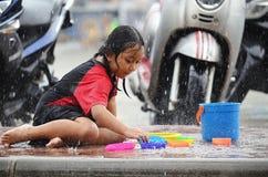Den unga asiatiska flickan väljer en leksak, som hon spelar i regnet under monsunsäsong i Thailand arkivbilder