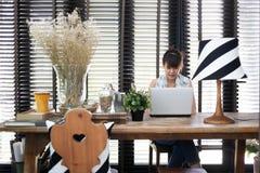 Den unga asiatiska funktionsdugliga kvinnan använder en bärbar dator Arkivfoto