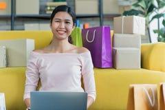 Den unga asiatiska härliga flickan är lyckligt le till att shoppa online-w royaltyfria foton