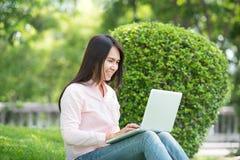 Den unga asiatiska härliga kvinnan med att le att arbeta för framsida som är utomhus- i ett offentligt, parkerar bärbar dator som fotografering för bildbyråer