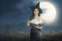 Den unga asiatiska häxakvinnan som läser passet, bokar arkivbild